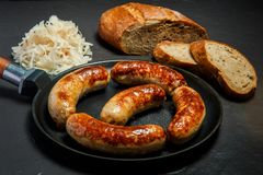 Five tasty ruddy meat wieners fried in large frying pan. Five tasty ruddy meat wieners fried in large pan served with sliced rye bread and sauerkraut on black royalty free stock images