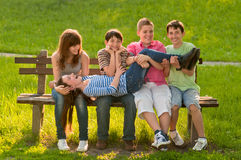 Five teenage boys and girls having fun in the park. On sunny spring day stock images