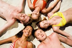 Five teens. Image of five happy teens lying on the sand Royalty Free Stock Image