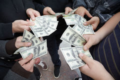 Five teens staying with funs of dollars in hands Stock Photos