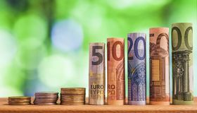 Five, ten, twenty, fifty and one hundred euro rolled bills banknotes, with euro coins on green blurred bokeh background. stock photo