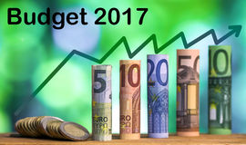 Five, ten, twenty, fifty and one hundred euro rolled bills bankn. Otes, with euro coins on green blurred bokeh background with `Budget 2017` and growth chart Stock Images