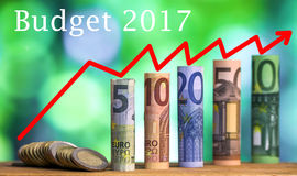 Five, ten, twenty, fifty and one hundred euro rolled bills bankn. Otes, with euro coins on green blurred bokeh background with `Budget 2017` and growth chart Stock Photography