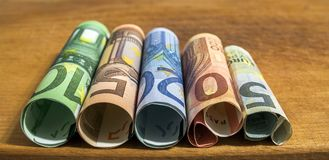 Five, ten, twenty, fifty and one hundred euro rolled bills bankn. Otes on wooden table background Stock Photo