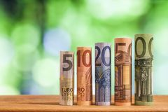 Five, ten, twenty, fifty and one hundred euro rolled bills bankn. Otes on green blurred bokeh background Stock Image