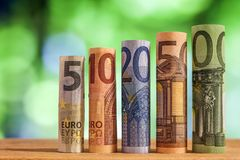 Five, ten, twenty, fifty and one hundred euro rolled bills bankn. Otes on green blurred bokeh background Royalty Free Stock Images