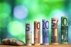 Five, ten, twenty, fifty and one hundred euro rolled bills banknotes, with euro coins on green blurred bokeh background. royalty free stock image