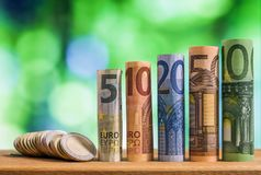 Five, ten, twenty, fifty and one hundred euro rolled bills banknotes, with euro coins on green blurred bokeh background. stock photography