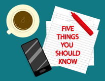 Five Things You Should Know. The phrase Five Things You Should Know in red text on lined notepaper with a cup of coffee, smartphone and marker pen on a desktop Royalty Free Stock Images