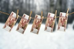 Five thousand russian rouble banknotes hanging on a clothesline with clothes pegs on blurred winter forest background. Woodworking industry concept Royalty Free Stock Images