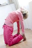 The Five Tibetan Rites. Mature Woman doing the five tibetan rites; third rite Stock Image