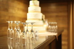 Five tiered wedding cake with empty champagne flutes on table Royalty Free Stock Photos