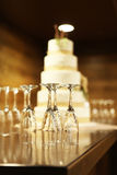 Five tiered wedding cake with empty champagne flutes on table Stock Image