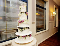 Five tiered white wedding cake with violet flowers Stock Images