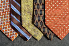 Five ties with a gray background. Five ties in brown, yellow, orange and beige tones, with assorted designs, on a gray background Royalty Free Stock Photos
