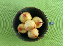 Five tiny Pears. Five pears in a green stilish cup. A plastic green table cloth is the background Royalty Free Stock Photography