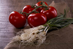Five tomatoes and fresh garlic from the garden stock photos