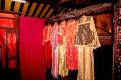Traditional Chinese Dresses. Five traditional Chinese dresses on display in a bedroom Gold dress and red dresses that are hanging from an old and faded wooded royalty free stock image