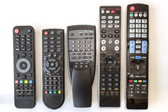 Five Used Remote Controls on White Background Stock Images