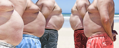 Five very obese fat men on the beach Royalty Free Stock Images
