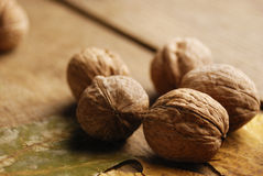 Five walnuts on the oak table Stock Photography