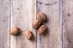 Five walnuts. On wooden table Stock Photos