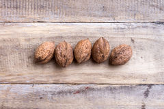 Five walnuts. On wooden table Royalty Free Stock Photo