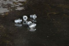 Five wheel nuts on the wetting ground Royalty Free Stock Images
