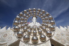 Five white buddha statues sitting well alignment in front of blue sky and decorating wonderful attractive mirror Royalty Free Stock Photos