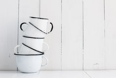 Five white enameled mugs. A stack of five white enameled mugs on painted wooden table, kitchen utensils and decor, rustic vintage kitchen background Royalty Free Stock Photos
