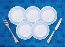 Five white plates. On restaurant table that is placed as the Olympic rings, and knife with fork Royalty Free Stock Photography