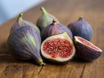 Five whole and one cut figs in a group close-up on a wooden table stock images