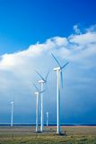 Five wind turbines on a blue s. Sea horizon, rural area, green field Royalty Free Stock Images
