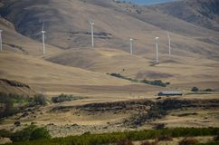 Five wind turbines on a desert hill slope. These are five wind turbines that generate electricity on the slope of a desert hill in  Washington in the Columbia Stock Image