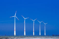 Five windmills ia a row in winter landscape Stock Photos
