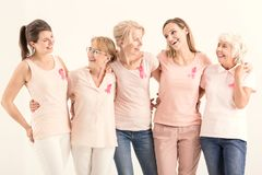 Five women with cancer ribbons. Smiling women of five generations with pink ribbons embracing each other, breast cancer concept stock photography