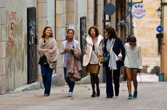 Five women walking on the street. Five young women are on the narrow street of Oviedo. Asturias. Northern Spain. Woman talking and laughing. The walls are spray stock photography