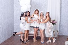 Five women in white celebrating with champagne Stock Images
