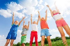Five wonderful children jumping in the air. On a green sunny meadow Stock Photo