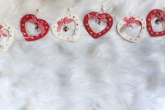 Five wooden heart shaped xmas ornaments on white soft fabric with ribbons royalty free stock photo