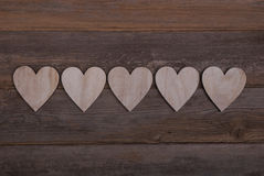 Five wooden hearts in a row on a wooden background. With space for text Stock Images