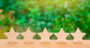 Five wooden stars. Get the fifth star. The concept of the rating of hotels and restaurants, the evaluation of critics and visitors. Quality level, good service stock photography