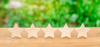 Five wooden stars. Get the fifth star. The concept of the rating of hotels and restaurants, the evaluation of critics and visitors. Quality level, good service stock image