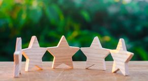 Five wooden stars. Get the fifth star. The concept of the rating of hotels and restaurants, the evaluation of critics and visitors. Quality level, good service stock photos
