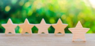 Five wooden stars. Get the fifth star. The concept of the rating of hotels and restaurants, the evaluation of critics and visitors. Quality level, good service stock photo