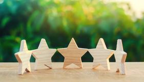 Five wooden stars. Get the fifth star. The concept of the rating of hotels and restaurants, the evaluation of critics and visitors. Quality level, good service royalty free stock photos