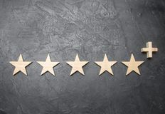 Five wooden stars and a plus, on a concrete gray background. The concept of the highest evaluation of quality and service. vector illustration