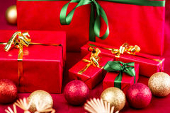 Five Xmas Gifts Wrapped in Plain Red. Five red Christmas presents placed on a red cloth. Bows in green and gold. Baubles and straw stars outside narrow depth of Royalty Free Stock Images