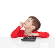 The five-year boy sitting at a white table and presses the button calculator Stock Photography