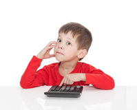 The five-year boy sitting at a white table and presses the button calculator Stock Photos